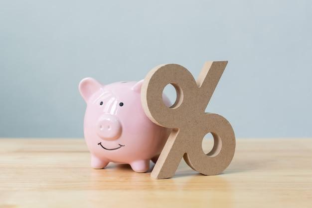 Simbolo del segno di percentuale e del porcellino salvadanaio sulla tavola di legno