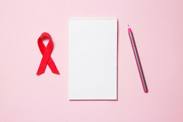 Simbolo della consapevolezza del cancro al seno con blocco note, penna, vista dall'alto, disteso. concetto di salute delle donne.