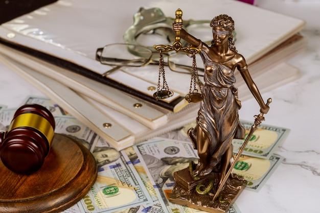 Simbolo della statua della giustizia dell'ufficio legislativo sul documento di legge sul lavoro con le manette della polizia del martelletto del giudice