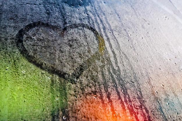 Simbolo di amore del cuore dipinto su vetro appannato illuminato da luci colorate