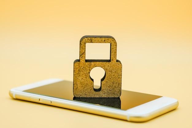 Simbolo di blocco chiave in legno su smart phone.