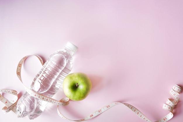 Simbolo di dieta piatto disteso un metro nastro e mela verde e una bottiglia di acqua