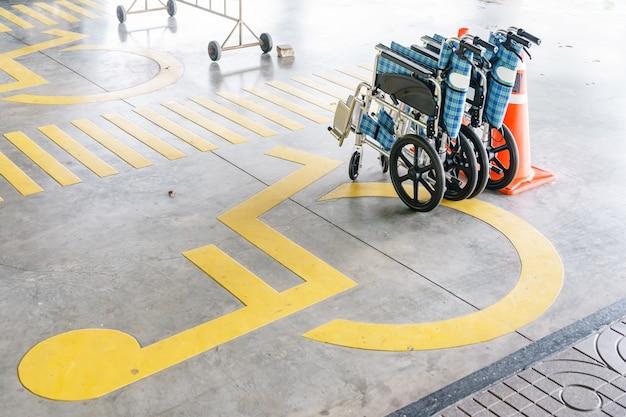 Simbolo di handicap su strada, traffico e pedoni sul parcheggio
