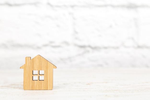 Simbolo di legno decorativo di una casa su priorità bassa bianca