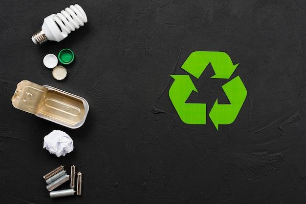 Simbolo di riciclaggio accanto a vari rifiuti