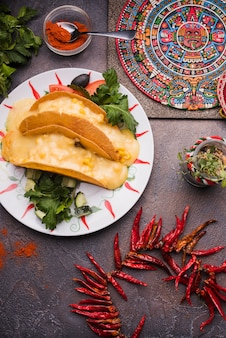 Simbolo messicano decorativo a bordo vicino al peperoncino rosso secco e pita con ripieno sul piatto