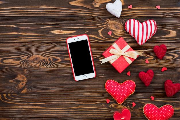 Simpatica composizione piatta con cuori rossi in tessuto fatti a mano e cellulare. contenitore di regalo rosso sulla tavola di legno. congratulazioni di buon compleanno o anniversario. modello romantico di storia d'amore con lo spazio della copia.