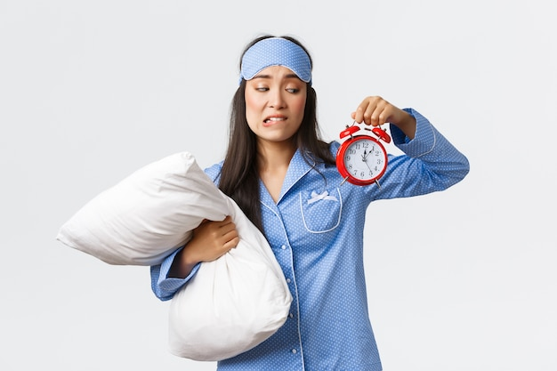 Simpatica studentessa asiatica si preoccupa di essere in ritardo all'esame mattutino, indossa pigiama e maschera per dormire, tiene in mano il cuscino e la sveglia con la faccia preoccupata e insicura, imposta la sveglia per svegliarsi presto