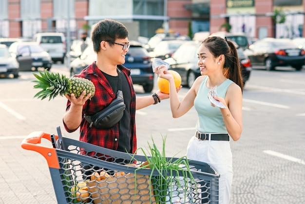 Simpatiche coppie asiatiche in piedi vicino al carrello, uomo detiene ananas e melone e bella donna conta le banconote di dollari usa.