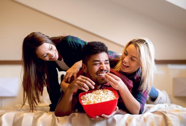 Simpatici amici che si divertono mangiando popcorn mentre guardano film affascinanti