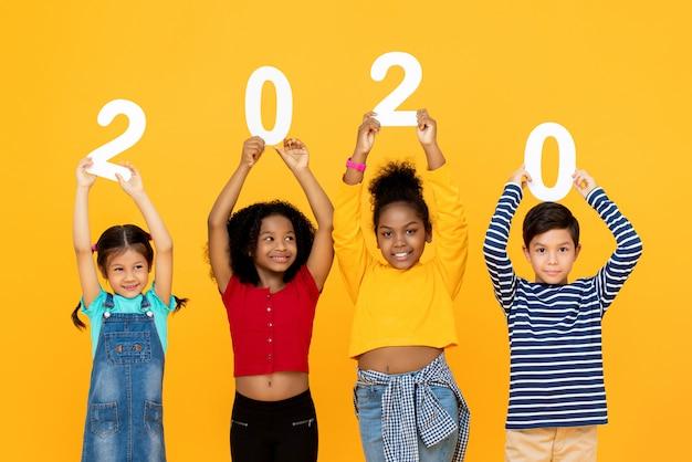 Simpatici bambini di razza mista sorridenti e in possesso di numeri 2020