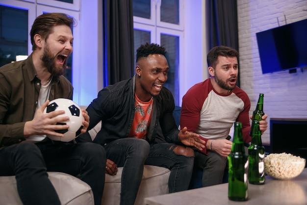 Simpatici giovani ragazzi multirazziali allegri che incoraggiano la loro squadra di calcio preferita con urla e mani in alto durante la visione di un gioco sportivo in tv