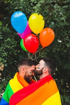Simpatici innamorati gay che abbraccia avvolti nella bandiera arcobaleno