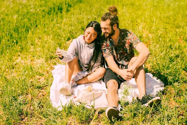Simpatici innamorati multietnici prendendo selfie in campo
