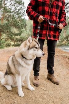 Simpatico cane husky seduto sul sentiero nel bosco o ambiente rurale mentre il suo proprietario lo tiene al guinzaglio durante il freddo