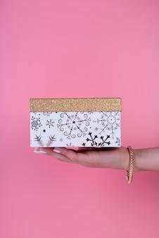 Simpatico contenitore di regalo tenuto in mano su sfondo rosa