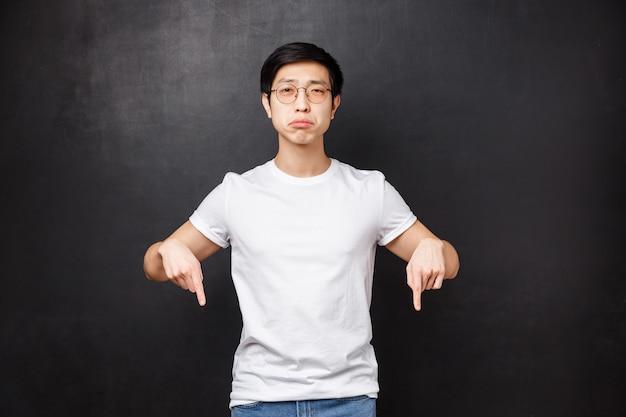 Simpatico e triste ragazzo asiatico triste e triste che singhiozza guarda la telecamera con rammarico e tristezza, punta le dita verso il basso per qualcosa di rotto o sconvolgente, si sente a disagio,