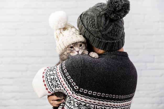 Simpatico gatto con cappello tenuto dal proprietario
