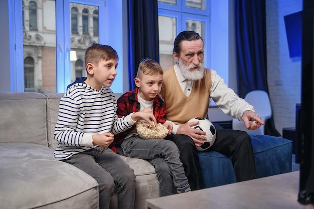 Simpatico nonno anziano con la barba concentrato con i suoi allegri nipoti che passano il loro tempo libero a rivedere la partita di basket in tv
