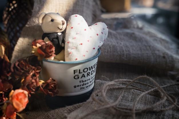 Simpatico orso di san valentino con cuore bianco in un secchio di alluminio. concetto di san valentino