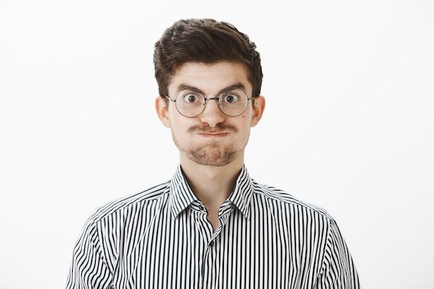 Simpatico ragazzo europeo con baffi e sopracciglia malate in occhiali alla moda, fare smorfie ed essere infantile, imbronciato, non avendo niente da fare, annoiato mentre lavora, in piedi sul muro grigio