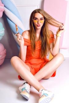 Simpatico ritratto di moda di bella donna bionda, decorazione dolcezza, colori pastello, posa sul pavimento e con in mano lecca-lecca, indossando abiti alla moda e scarpe da ginnastica, sorridente e divertente.