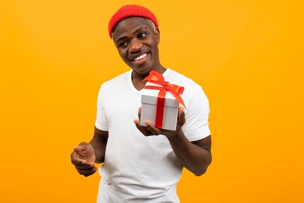 Simpatico uomo nero africano con un sorriso in una maglietta bianca tiene fuori una scatola un regalo con un nastro rosso per san valentino su uno sfondo giallo