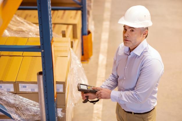 Simpatico uomo professionale che utilizza uno scanner durante il controllo dell'inventario