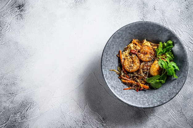 Singapore mei fun. tagliatelle di riso con gamberi, gamberi, carne di maiale, carota, cipolla, cavolo di napa. sfondo bianco. vista dall'alto. copia spazio