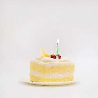 Singola candela sopra la fetta di torta su sfondo bianco