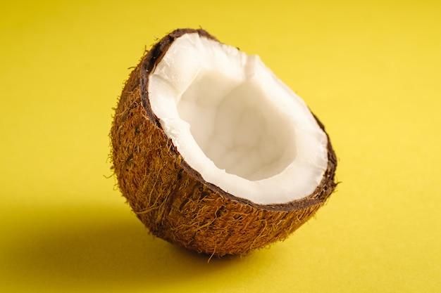 Singola frutta della noce di cocco sulla superficie normale gialla, concetto tropicale dell'alimento astratto, macro di vista di angolo