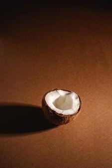 Singola frutta della noce di cocco sulla superficie normale marrone, concetto tropicale dell'alimento astratto, spazio della copia di vista di angolo