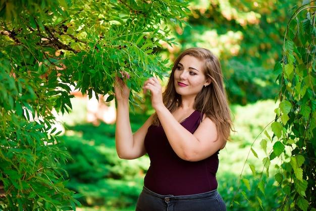 Singola giovane donna di risata sorridente felice sorridente caucasica abbastanza più di dimensione della ragazza, camminante nella foresta verde di estate. divertimento goditi la natura estiva all'aperto.