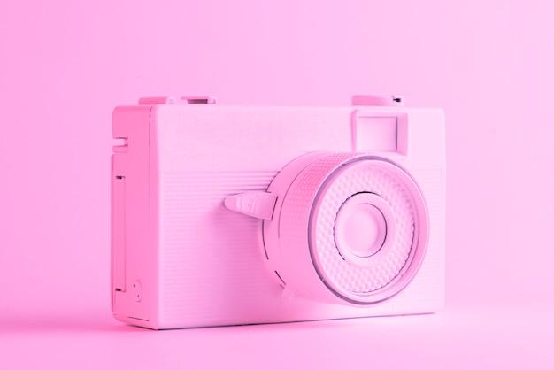 Singola macchina fotografica verniciata contro il contesto rosa colorato