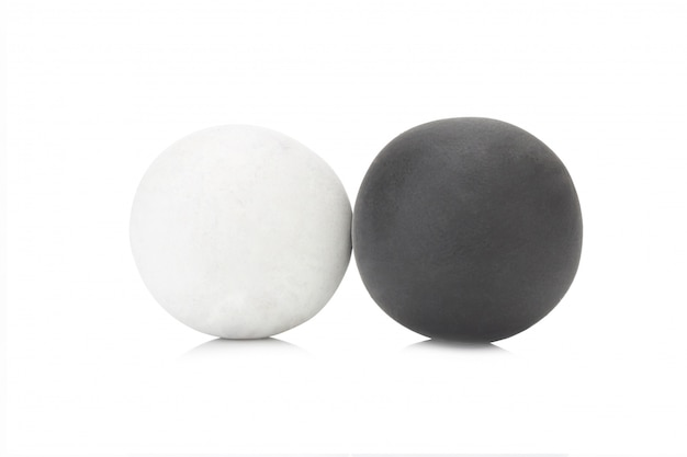 Singola palla in bianco e nero dell'argilla della plastilina sul primo piano bianco del fondo