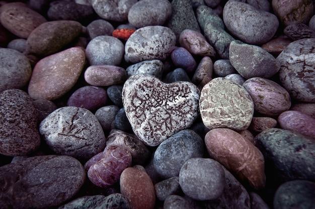 Singolo cuore su pietre di ghiaia nere, natura morta.