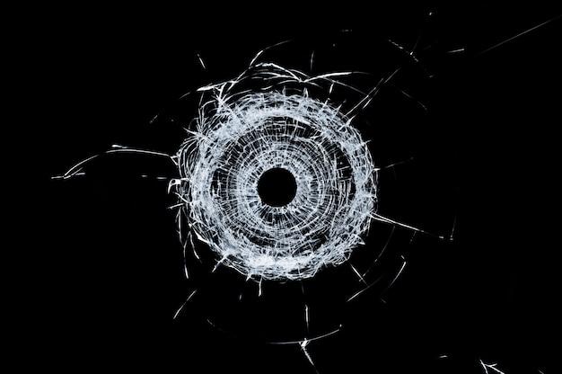 Singolo foro di proiettile di vetro rotto in vetro isolato sul nero