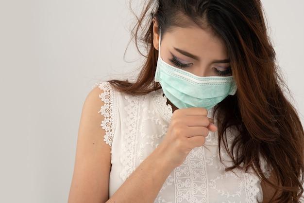 Sintomo di raffreddore o di allergia di influenza, giovane donna asiatica ammalata che starnutisce nell'isolato della mascherina su bianco