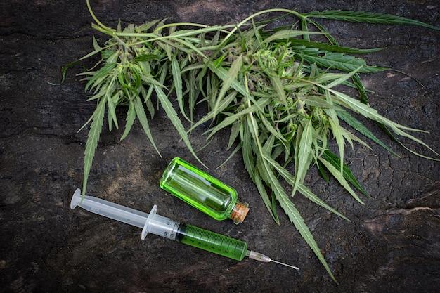 Siringa c'è medicina dentro sul tavolo di legno a sfondo di cannabis