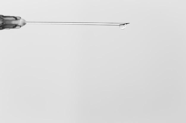 Siringa con goccia isolata su bianco