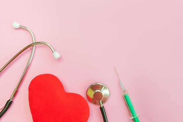 Siringa dello stetoscopio dell'attrezzatura della medicina e cuore rosso isolati su fondo rosa