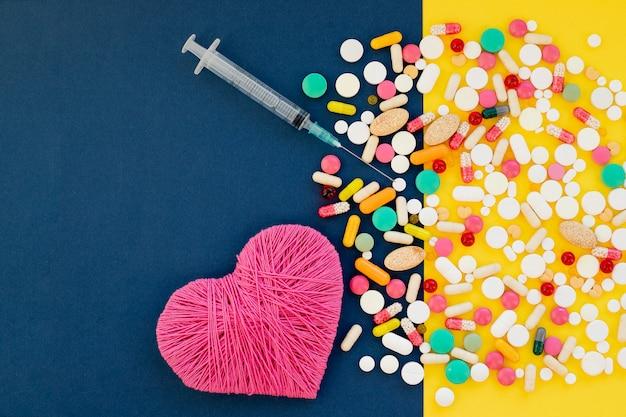 Siringa e pillole differenti, cuore sulla parete gialla blu. vista dall'alto con copia spazio trattamento e prevenzione del concetto di malattia cardiaca, pillole a forma di cuore, siringa, medicina farmaceutica
