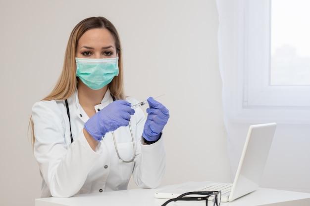 Siringa femminile della tenuta di medico con l'iniezione