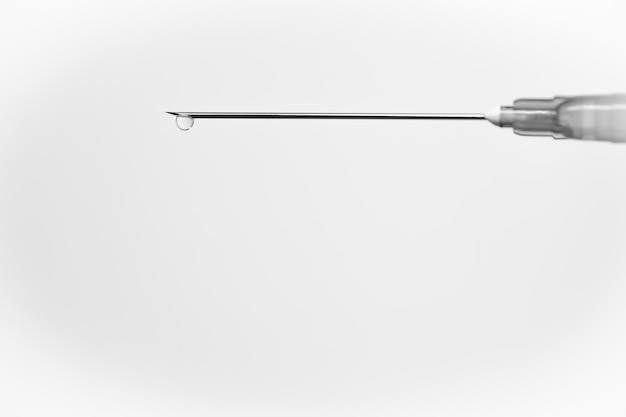 Siringa medica bianca con una goccia, isolata su bianco