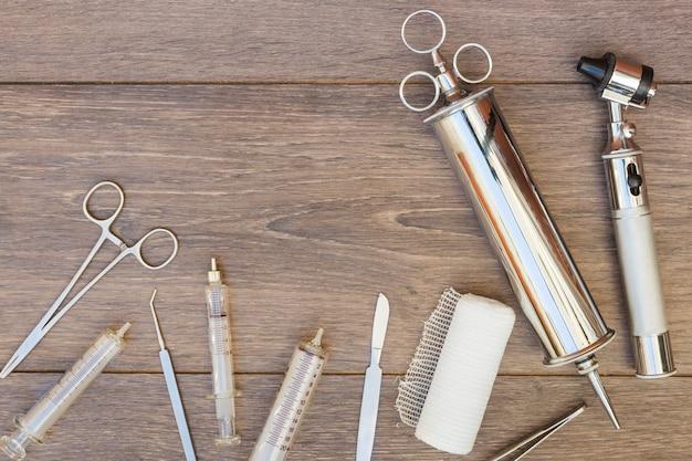 Siringa vintage in acciaio inossidabile; otoscopio e attrezzature mediche sulla scrivania in legno