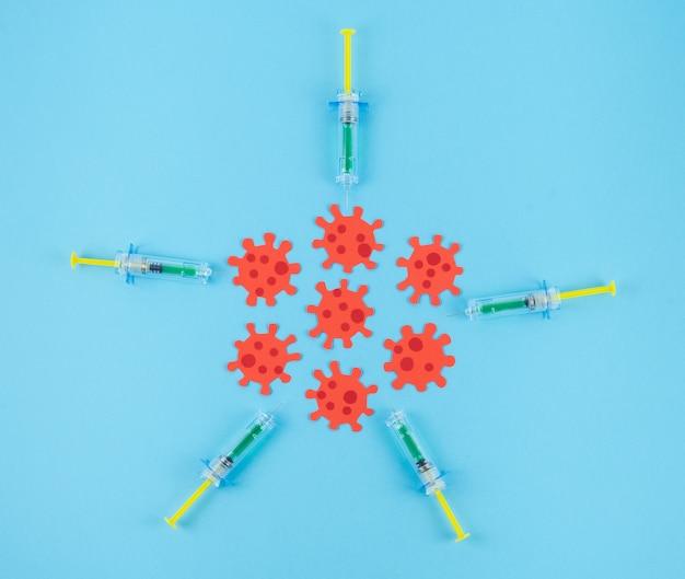 Siringhe che circondano i cluster di virus rossi su un tavolo blu. concetto di vaccino covid-19.