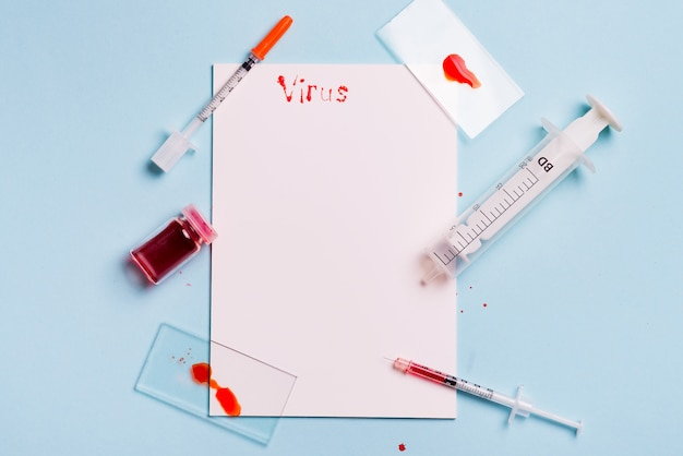 Siringhe e provetta con sangue su uno sfondo blu con carta bianca e la scritta virus