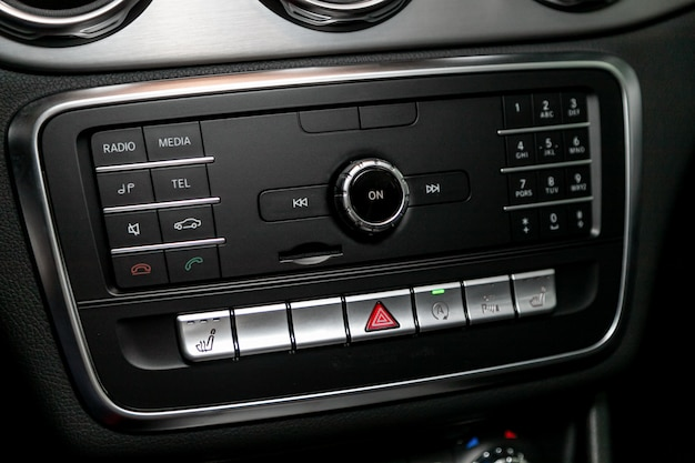 Sistema audio stereo, pannello di controllo e cd in un'auto moderna. pannello di controllo dell'automobile del lettore audio e di altri dispositivi
