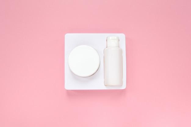 Sistema di cura della pelle a casa, crema e tonico in confezione bianca su sfondo rosa pastello.