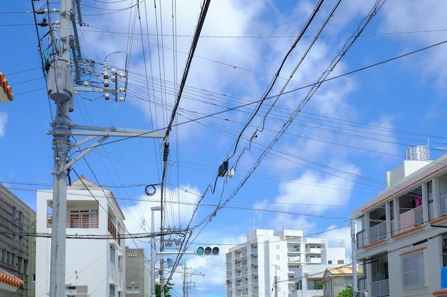 Sistema di elettricità per uso in città del giappone con il fondo del cielo blu e della nuvola.